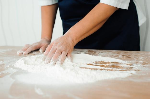 De chef-kok bereidt het deeg - het proces van het maken van deeg in de keuken