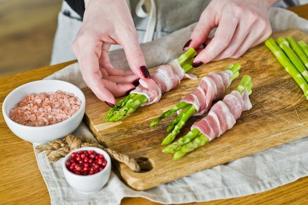 De chef-kok bereidt mini-asperges in spek. zijaanzicht, concept het koken voedsel evenwichtig dieet.