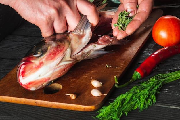 De chef-kok bereidt verse vis grootkopkarper met kruiden. voorbereiden om visvoer te koken. werkomgeving in de restaurant- of cafékeuken