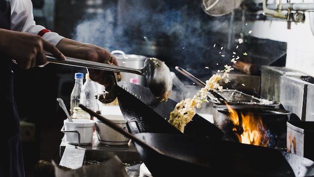 De chef-kok beweegt gebraden gerecht het koken bij wok