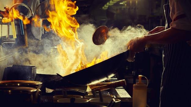 De chef-kok beweegt gebraden gerecht in wok