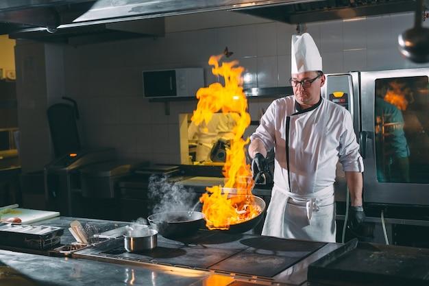 De chef-kok beweegt groenten in wok.