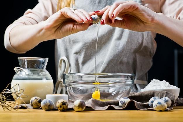 De chef-kok breekt een kwartel-ei in een kom.