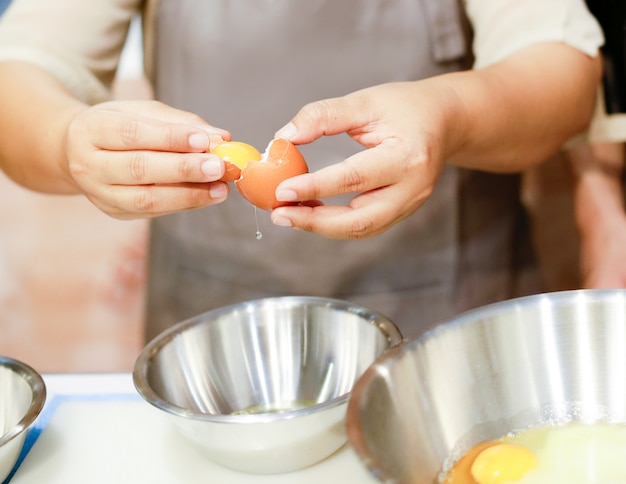 De chef-kok breekt het ei in een glaskom, scheidend de dooier van het ei