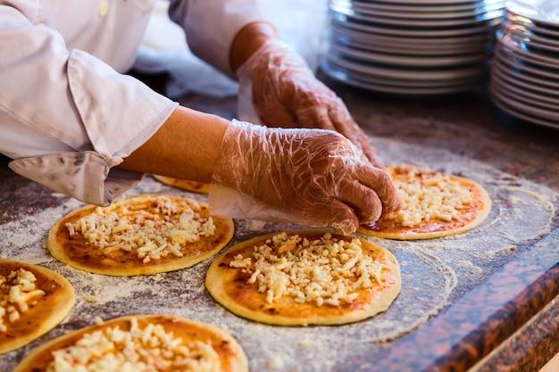 De chef-kok, die toppings op een pizza legt