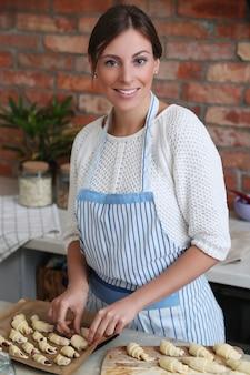 De chef-kok die van het vrouwengebakje croissants maken
