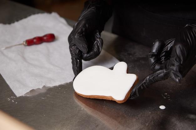 De chef-kok dient handschoenen in de keuken in die koekjes voorbereidt