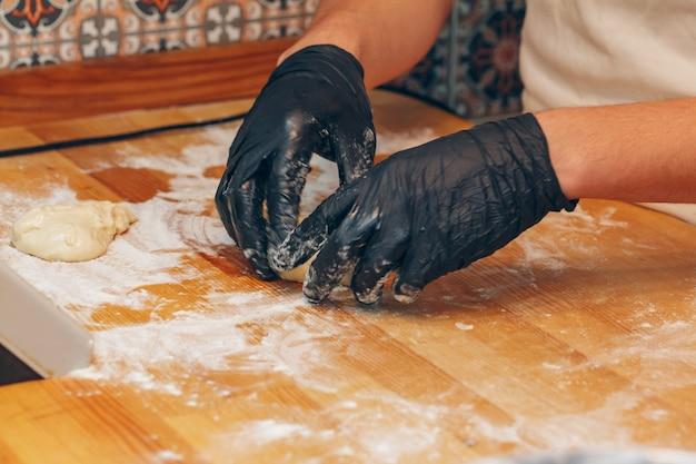 De chef-kok dient zwarte handschoenen in bereidt deeg dicht omhoog voor