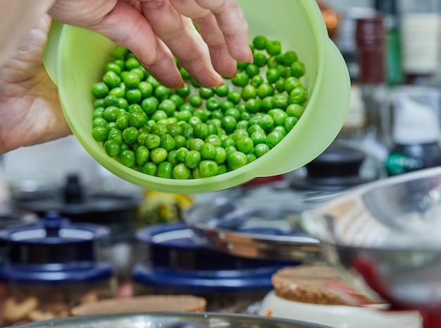 De chef-kok doet groene erwten in een kom om gebakken goederen met asperges en erwten te maken. stap voor stap recept.