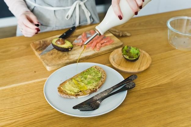 De chef-kok giet olijfolie toast met avacado op een zwarte toast van brood.