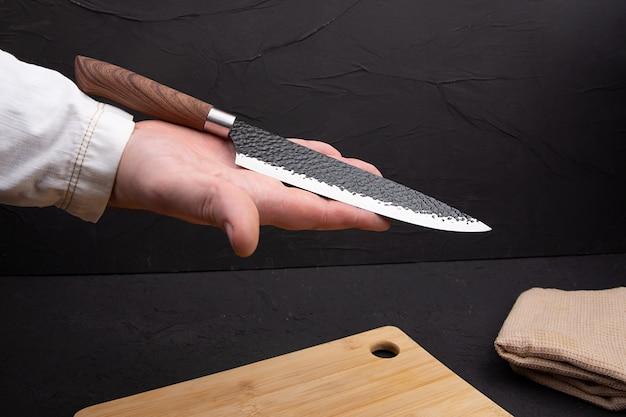 De chef-kok houdt een mes in zijn hand