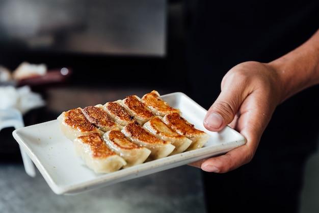 De chef-kok houdt een plaat van yaki-gyoza-reeks