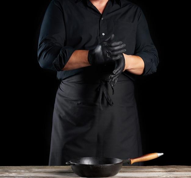 De chef-kok in zwart overhemd en schort zet zwarte latexhandschoenen op zijn handen alvorens voedsel, zwarte achtergrond voor te bereiden