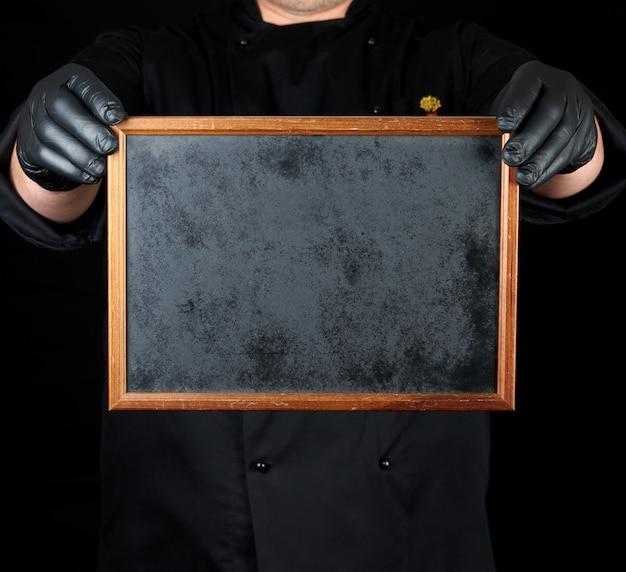 De chef-kok in zwarte eenvormige en zwarte latexhandschoenen houdt een leeg houten kader
