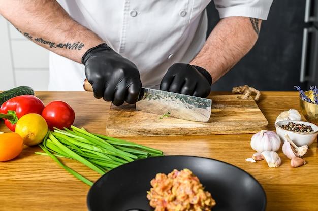 De chef-kok in zwarte handschoenen bereidt tartaar van verse tonijn