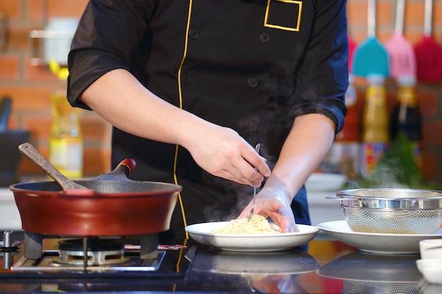 De chef-kok kokende spaghetti van de close-uphand dichtbij pottenpan op het gasfornuis in keuken