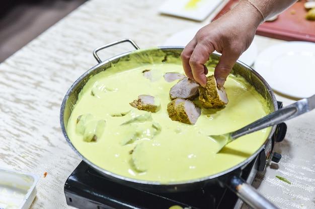 De chef-kok kookt vlees met groenten in pan