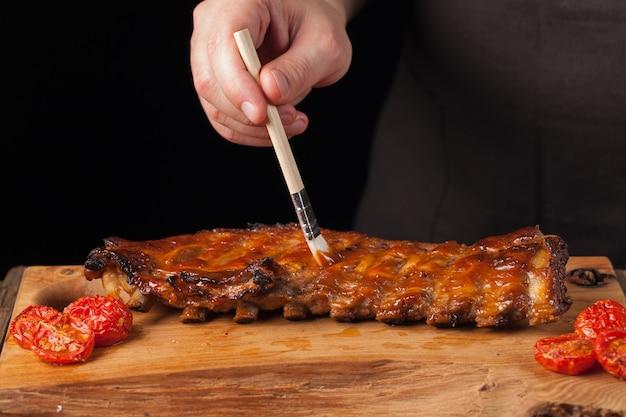 De chef-kok krijgt bbq-saus op kant-en-klare varkensribbetjes.