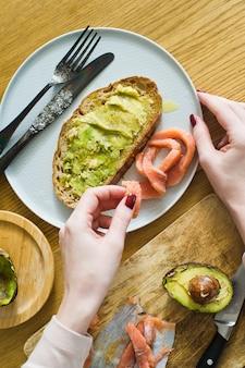 De chef-kok legt de zalm op toast met avacado op een zwarte toast van brood.