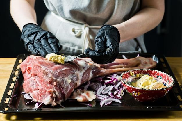 De chef-kok marineert de rauwe lamsbout.