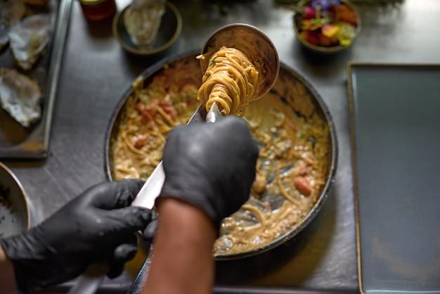 De chef-kok mengt spaghetti in een pan de tomaten en oesters, gerecht in een restaurant.