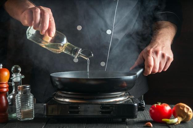 De chef-kok of kok voegt tijdens het koken olijfolie toe aan de pan. werkomgeving aan de keukentafel van het restaurant