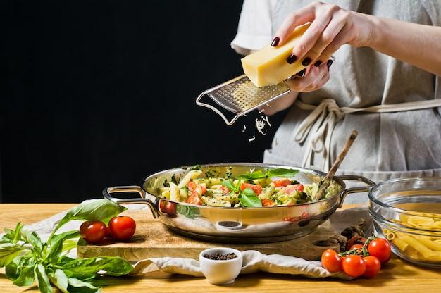 De chef-kok raspt parmezaanse kaas in de pan met pasta.