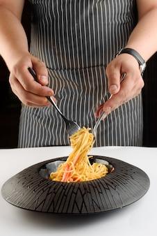 De chef-kok roert spaghetti met kaas, witte saus en kerstomaatjes met een vork en mes in een zwarte plaat op een witte tafel.