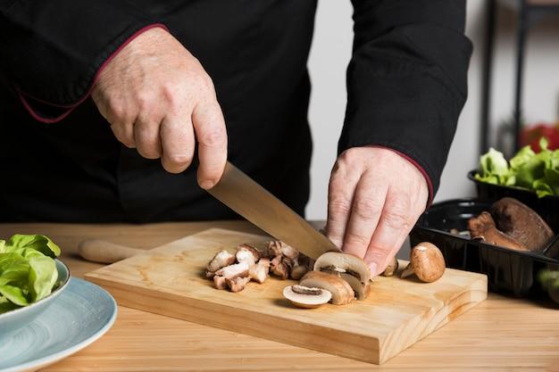 De chef-kok snijdende paddestoelen van de close-up