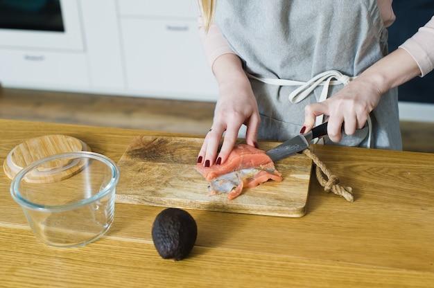 De chef-kok snijdt atlantische zalm voor een broodje met avacado en ei.