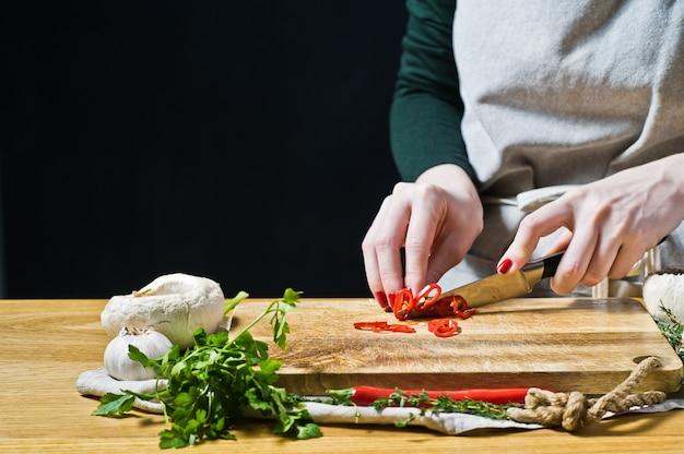 De chef-kok snijdt de chili-peper