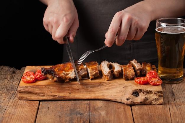 De chef-kok snijdt mes klaar om varkensribben te eten.