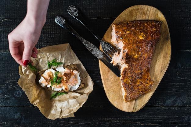 De chef-kok strooit peterselie op een broodje met gerookte zalmfilet op zwart brood en zachte kaas