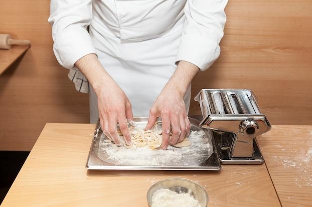 De chef-kok van het restaurant bereidt een portie traditionele italiaanse pasta. masterclass.