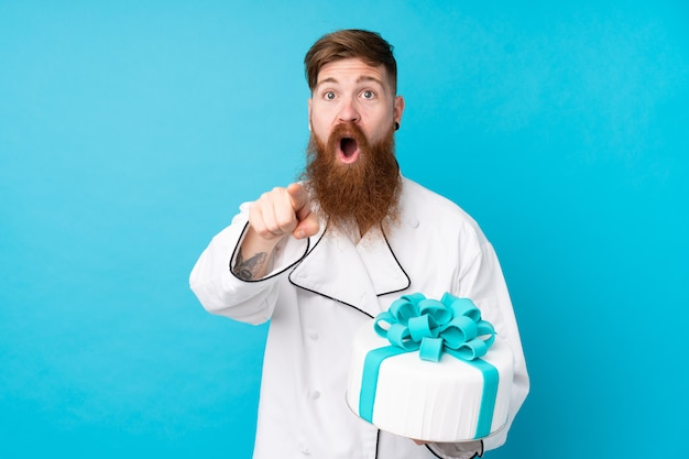 De chef-kok van het roodharigebakje met lange baard die een grote cake over geïsoleerde blauwe muur houden verrast en voorzijde richten