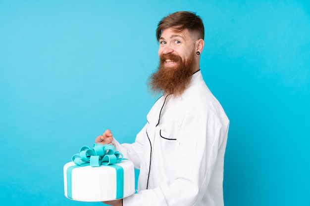 De chef-kok van het roodharigegebakje met lange baard die een grote cake over geïsoleerde blauwe muur houden en het richten