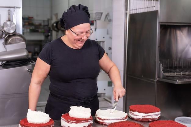 De chef-kok van het vrouwengebakje die en gelukkig glimlachen werken, makend cakes bij de patisserie.
