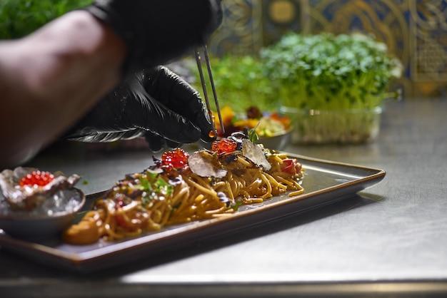 De chef-kok versiert met rode kaviaar een schaal met zeevruchten spaghetti, selectieve aandacht.