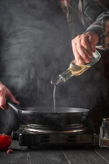 De chef-kok voegt tijdens het koken olijfolie toe aan de pan