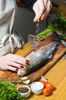 De chef-kok zouten rauwe forel op een houten snijplank.
