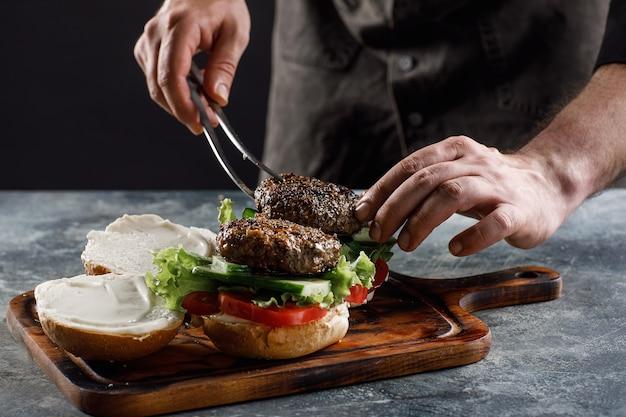 De chef kookt hamburgers in het restaurant