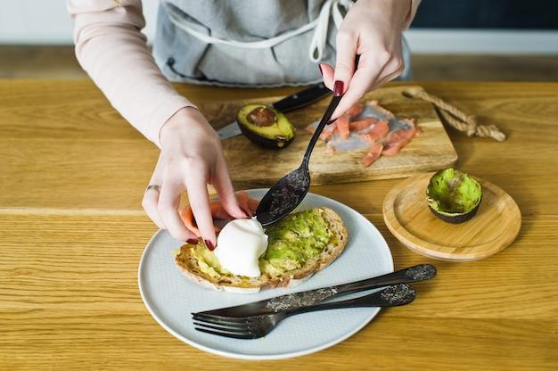 De chef legt een ei op toast met avacado en zalm op zwart brood.