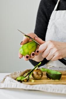 De chef pelt avocado op een houten snijplank.