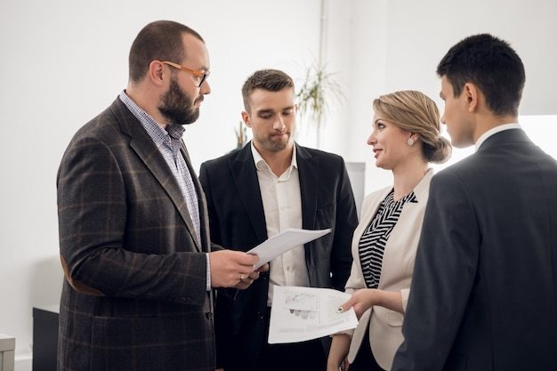 De chef van het bouwbedrijf houdt een vaste vergadering met ondergeschikten, geeft instructies en eist een verslag van de werkzaamheden op kantoor.
