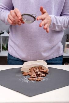 De chef van het gebakje bestrooit koekjes met poedersuiker. verticaal frame. werkwijze