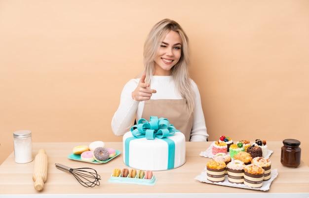 De chef van het tienergebakje met een grote cake in een lijst richt vinger op u