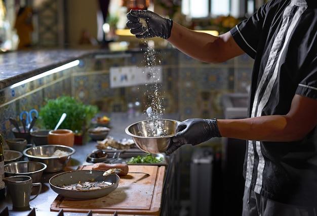 De chef voegt parmezaanse kaas toe, het proces van het koken van spaghetti met zeevruchten
