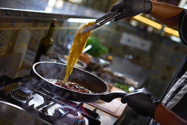 De chef voegt spaghettibakken toe in een pan de tomaten en oesters,