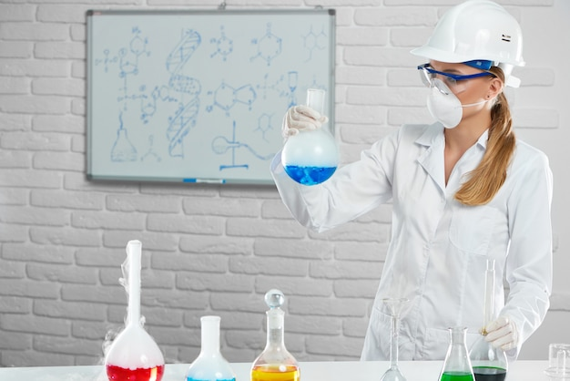 De chemicus werkt met chemische stoffen die beschermingsmiddelen dragen