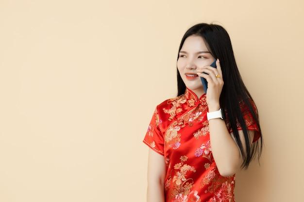 De chinese telefoon die van het tienermeisje met vriend de traditionele doek van qipao kleden.